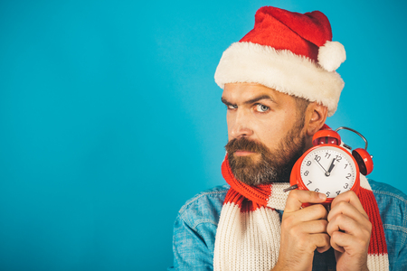 Christmas man hold alarm clock. Time to celebrate concept. New year, xmas holidays celebration. Countdown to midnight. Hipster in santa hat, scarf on blue background, copy space