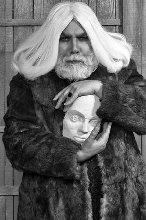 木製の背景にリングで白い彫刻の頭を持つ毛皮のコートで深刻な顔と髪に長いひげを持つ古いドルイドひげの男 写真素材
