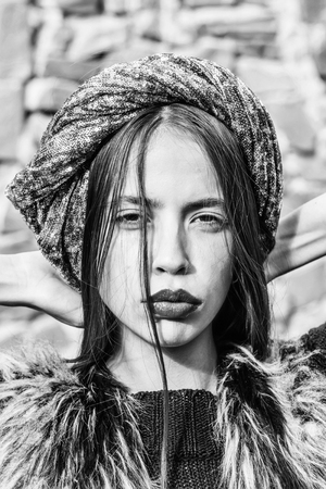modieuze jonge sexy vrouw of meisje met oranje lippen op mooi gezicht en lang donkerbruin haar in grijze pailletten hoed of tulband en bont vest buiten op onscherpe achtergrond