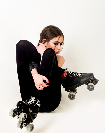 Girl with roller skates shoes on legs sit on white background. Skating, sport, recreation, activity, lifestyle, energy concept