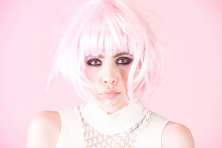 Hairdressing, beauty salon. Woman wear pink wig hair on rosy background. Girl with smokey eyes, makeup face. Fashion, style, visage. Fake, false concept.