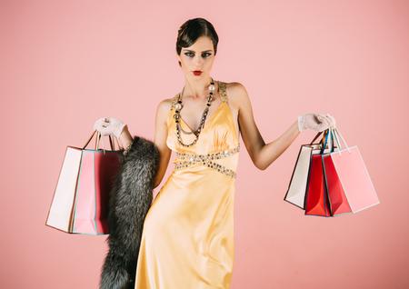美しさとヴィンテージファッション。ショッピング、レトロな外観、ピンナップ。ピンクの背景にかわいいファッションモデルをピンアップ。レト 写真素材