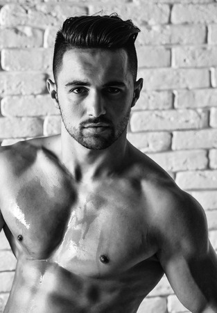 Handsome man or muscular macho, bodybuilder, with sexy, muscle torso, body, with six packs and abs poses on white brick wall