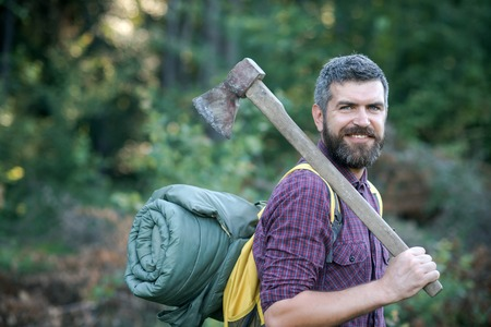 Hipster lumberjack with beard and smile hold tourist backpack and axe on shoulder on summer day on natural landscape. Logging and chopping concept. Stock Photo