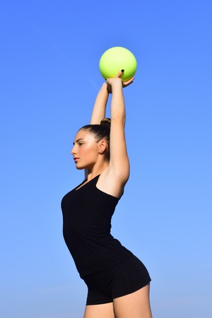 Sport and success. Woman gymnast in black sportswear with green ball. Gymnastic school and energy. Workout of girl on blue sky background. Flexibility in acrobatics and fitness health. Stock Photo