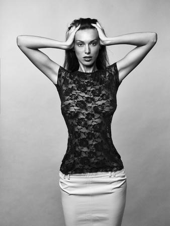 Guipure 赤いブラウスとタイトなスカートのかなりブルネットの女性は彼女の腕を上げ、灰色のスタジオの背景に彼女の頭を保持します 写真素材