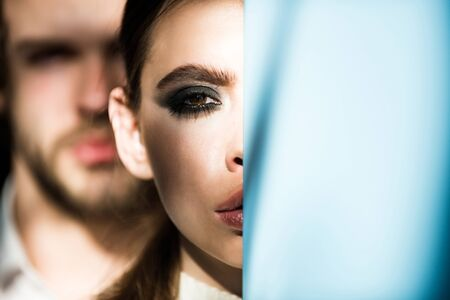 relaciones sexuales: Girl hide half face makeup at blue wall and blurred macho on background. Fashion, beauty, relationship concept, copy space Foto de archivo
