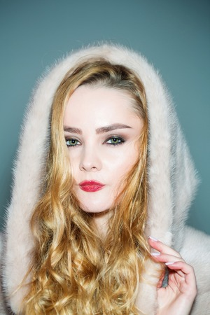 Girl in mink fur coat and hood on head. Woman with makeup face and long blond hair, hairstyle. Fashion, style, winter clothing concept