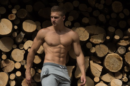 Athlete or bodybuilder on firewood background. Man with ab, six pack torso stand at wood stack. Energy, strength concept. Forestry, timber harvesting. Ecology, nature, environment.