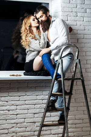Couple in love hug on window sill. Woman with long hair and man hipster on stepladder. Future, dreams, success concept. Relationship, affection, flirt.