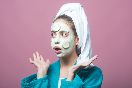 Woman with cucumber mask on surprised face on violet background. Rejuvenation, health, youth. Beauty salon concept. Skin and hair care, spa, wellness. Girl with bath towel on head. 免版税图像