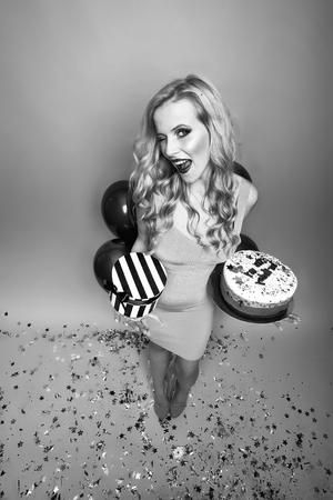 One pretty emotional young smiling blonde woman with long curly hair holding birthday cake with candles near bunch of red balloons with confetti and gift box in studio on yellow backdrop, vertical