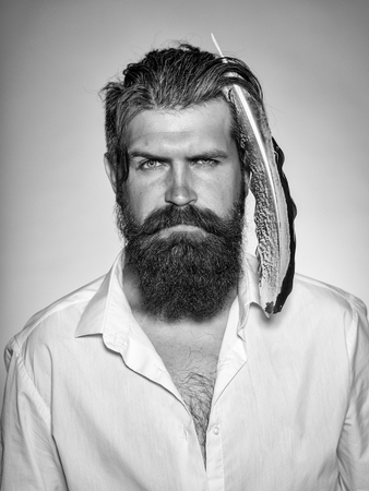 Handsome young stylish hipster man with long beard and big feather in hair in white shirt standing in studio on grey background Stok Fotoğraf