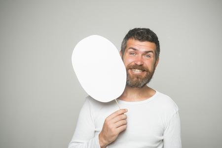 幸せそうな顔で流行に敏感な紙の銘板を保持します。長いひげと口ひげを持つ男。感覚や感情。男や背景が灰色のひげを生やした男。理容ファッシ