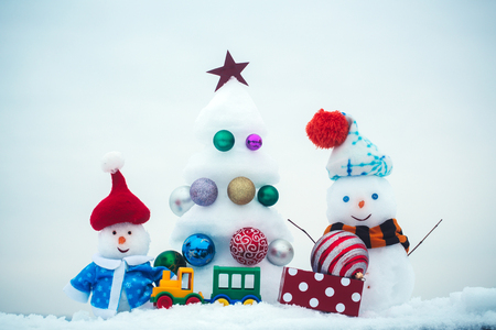 Snowmen with smiley faces in clothing. xmas and new year. Christmas tree with ball decorations, toy train and present box. Winter holidays concept. Snow sculptures on white background.