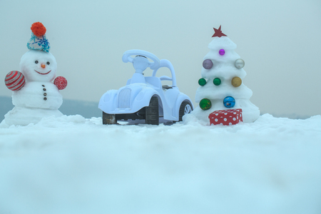 smiley face car: Snowman and toy car on snowy background. Snow sculpture with smiley face on winter day. xmas and new year. Christmas tree and present box on grey sky. Holidays celebration concept.