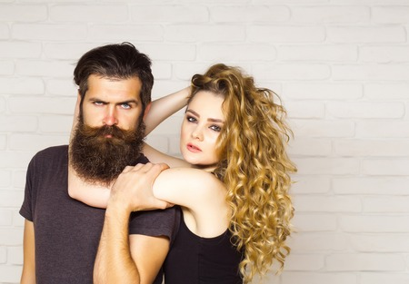Girl and bearded hipster. Hipsterism, subculture, trend. Fashion, beauty, style concept. Man with beard and woman with long blond hair. Couple in love hug on white brick wall.