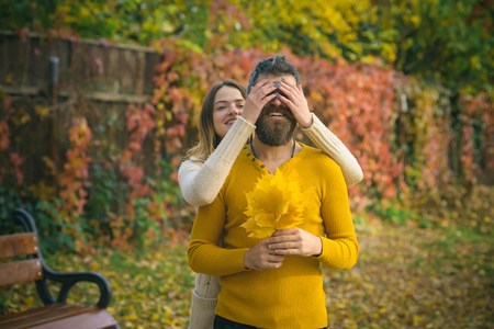 Autumn happy couple of girl and man outdoor. Couple in love in autumn park. Love relationship and romance. Man and woman at yellow tree leaves. Nature season and fall holiday.