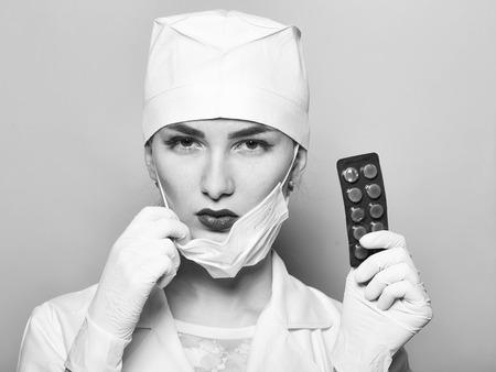 Médica no uniforme branco médico segurando pílulas no estúdio em fundo amarelo Foto de archivo - 91538105