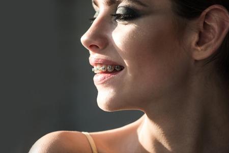 少女や女性の歯にブレースと笑顔します。歯科治療のコンセプトです。口腔病学、矯正、健康、美容。 写真素材