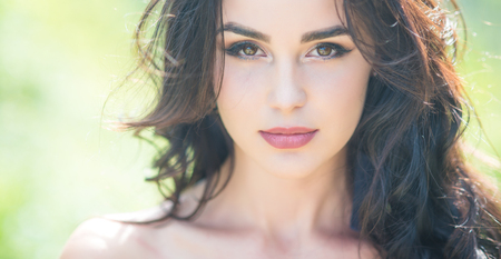 Girl face with makeup on young skin in nature. Woman with long brunette hair on sunny day. Skincare, youth, health concept. Fashion, beauty, visage.