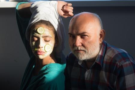 顔にキュウリのマスク、頭にタオルを付ける女性。あごひげと大胆な額を持つ少女と老人。若さ、美しさ、新鮮さ、若返り、腐敗、老化、年齢の概