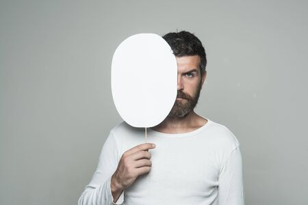 Barber fashion and beauty. Feeling and emotions. Hipster with serious face hold paper nameplate. Man with long beard and mustache. Guy or bearded man on grey background., copy space Banco de Imagens