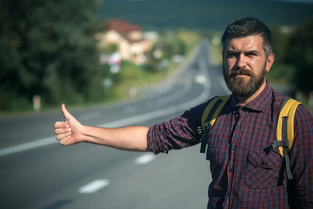 Hipster hiker show thumbs up hand gesture on sunny day. Summer vacation concept. Adventure, discovery, wanderlust. Man with backpack hitchhiking on road. Tourist traveler travel auto stop.