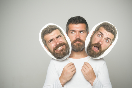 Guy or bearded man on grey background. Man with long beard and mustache. Barber fashion and beauty. Hipster with scary, surprised and serious face hold portrait nameplate. Feeling and emotions.