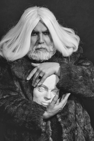 真剣な顔、暗い背景上のリングが付いている手の白い彫刻の頭を保持の毛皮のコートで髪の長いひげを生やした古いドルイド