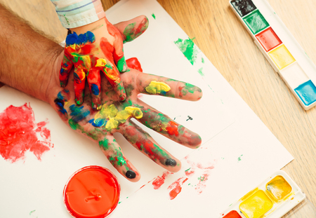 Hands in colorful paints and multicolor palette on white paper. Arts and handprint painting. Care, love or adoption concept. Fathers day and family. Support and protection. Stock Photo