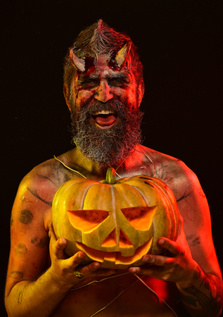 Halloween trick or treat. Devil smile with jack o lantern. Man demon hold pumpkin on black background. Darkness and light concept. Satan with bloody horns, beard, red blood, wounds.