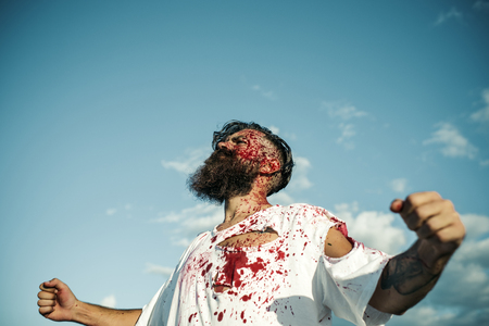 Halloween man bleeding with red blood in torn tshirt standing with fists hands on sunny day on blue sky. Rescue and liberation concept. War and peace.