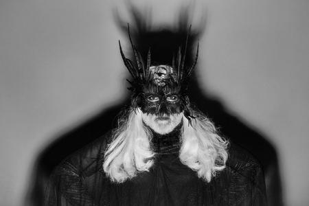 긴 흰 머리와 깃털과 회색 배경에 그 뒤에 큰 의상을 입고 검은 색 의상 넓은 어깨와 노란색 크라운 어두운 마스크에 수염을 가진 악마 마법사 남자