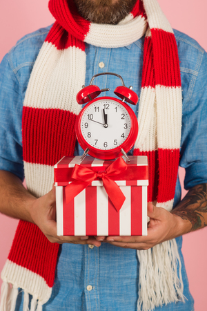 Christmas present box with red alarm clock in male hands on pink background. Boxing day concept. Time to celebrate xmas, new year, winter holidays Stock Photo