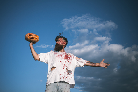 symbol victim: Halloween soldier zombie with red blood on cloudy blue sky. Man holding pumpkin on hand. War victim and horror concept. Hipster in bloody torn tshirt with jack o lantern. Autumn holiday celebration.