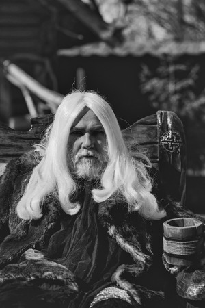 Druid old man with long silver hair beard in fur coat sits in chair with wooden mug on blurred background Reklamní fotografie