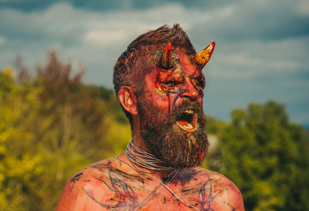 Halloween demon man with open mouth. Dragon creature on natural environment. Temptation, hell, evil, horror concept. Satan with red blood and wounds on face skin. Devil head with bloody horns. Stock Photo