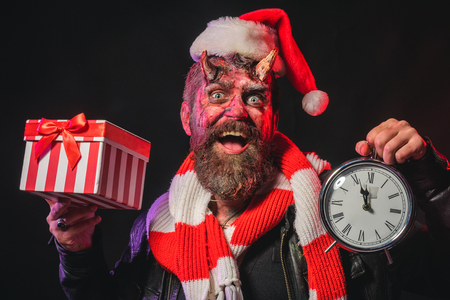 Halloween or christmas man devil hold present box and clock. Hipster smile with satan horns in santa hat. Boxing day, black friday, sale concept. Time to celebrate.