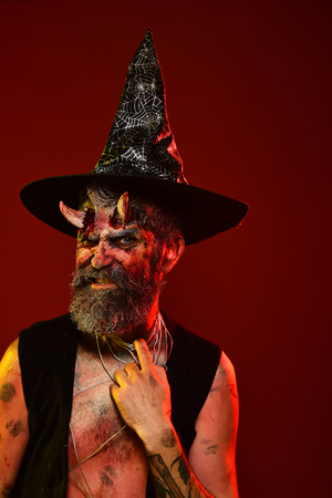 Halloween man with satan horns in witch hat on head. Devil hipster with beard, blood, wounds on face on red background. Hell, death, evil, horror concept. Might, magic, witchcraft Stock Photo