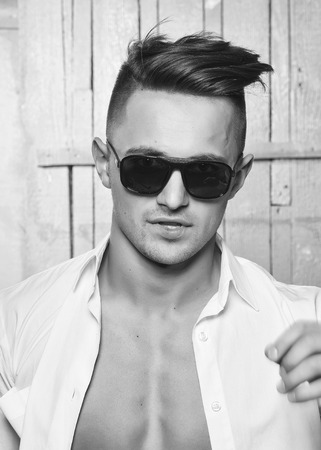 Sexy serious sensual muscular young macho man with bare torso in white shirt and sun glasses standing indoor on wooden background, vertical picture Zdjęcie Seryjne