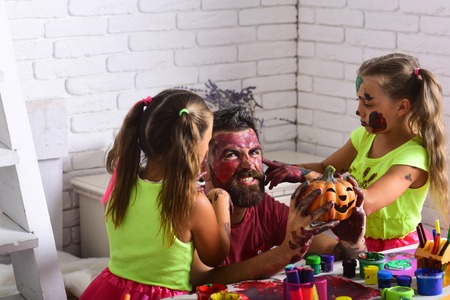 Halloween children with happy face in paint. Kids or small girls with bearded man father hold pumpkin. Halloween family with colorful paint. Holiday and party celebration. Art and color painting.