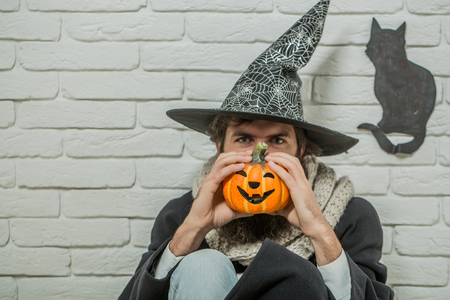 Halloween man in witch hat sitting on floor. Autumn holidays celebration. Evil spell and magic. Bad luck concept. Hipster with pumpkin and black cat symbol on wall. Stock Photo