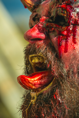 Halloween vampire man face with bloody tongue, beard and bleeding red blood. Sucking life force concept. Cosplay and holiday celebration