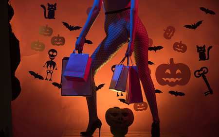 Halloween Legs of girl on skeleton and bat background. Halloween Holiday celebration. shopping and party package. sexy legs in fishnet tights and shoes. buttocks of woman at pumpkin hold shopping bag.