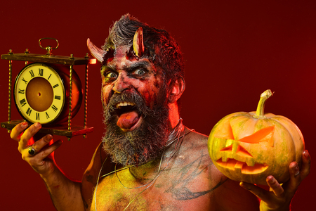 Halloween autumn holidays concept. Man demon hold pumpkin and clock. Satan show tongue with beard, wounds, blood, tattoo on chest. Devil with bloody horns on red background. Time to celebrate. Stock Photo