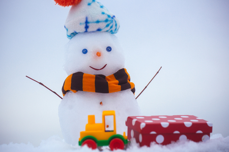 Snowman in hat and scarf on white background. Snow sculpture with smiley face. Toy train and red present box. Christmas and new year. Winter holidays celebration concept.