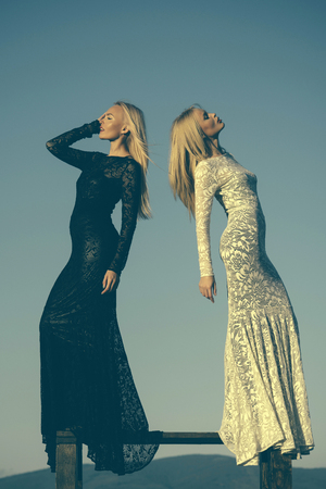 Opposites and contrasts concept. Women wearing black and white dresses. Two girls with long blond hair posing on blue sky. Fashion and beauty. Choice, decision and future.