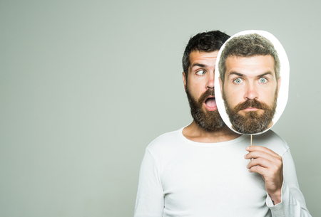 Barber fashion and beauty. Feeling and emotions. Guy or bearded man on grey background. Man with long beard and mustache. Hipster with surprised and serious face hold portrait nameplate., copy space Banco de Imagens