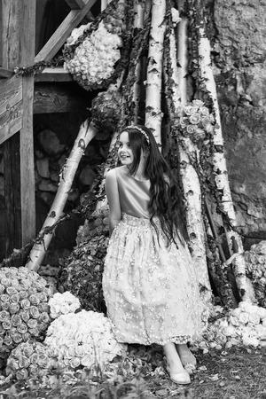 ドレスと長いブルネットの髪と花飾り屋外と木製の階段近くに立っている顔を笑顔と花輪のかわいい女の子